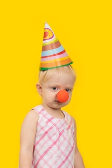 Portrait of funny girl with party hat and red clown nose on yellow space. vertical frame.