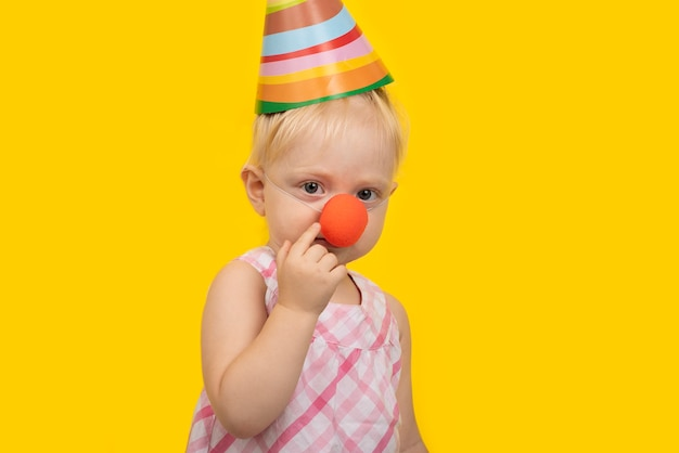 Portrait of funny girl with party hat and red clown nose on yellow space.