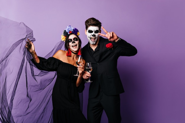 Portrait of funny guy and girl with painted faces, having fun with glasses of wine at halloween party.