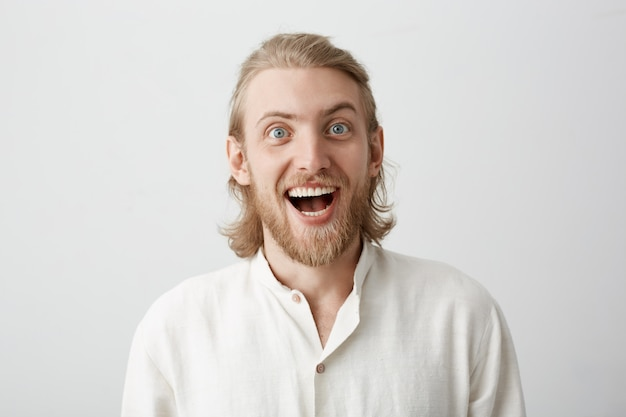 Portrait of funny handsome bearded guy with fair hair making faces as if acting crazy