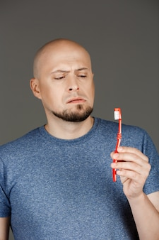 Portrait of funny handsome man in grey shirt holding toothbrush over dark wall