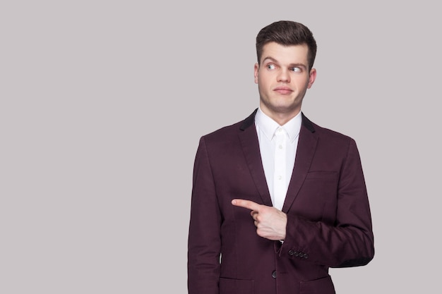 Portrait of funny handsome young man in violet suit and white shirt, standing, pointing and looking away with funny face and smiling. indoor studio shot, isolated on grey background.