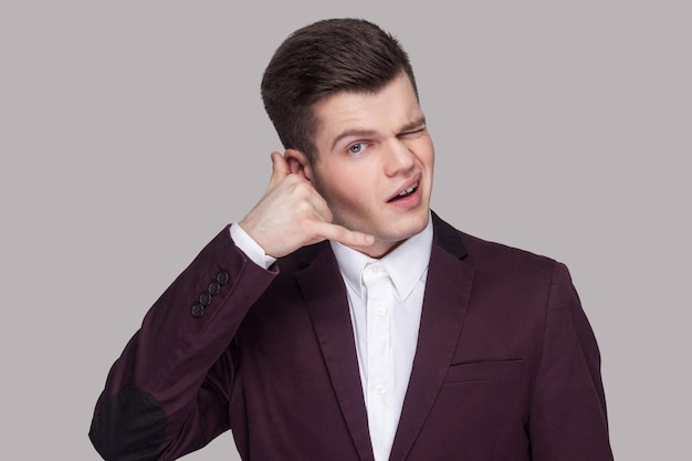 Portrait of funny handsome young man in violet suit and white shirt, standing with hands near face and looking at camera with call gesture. indoor studio shot, isolated on grey background.