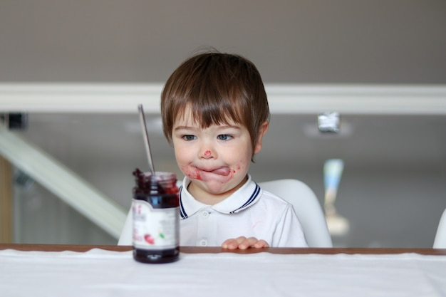Portrait of funny little boy looking at glass jar with cherry jam with his tongue out and dirty face