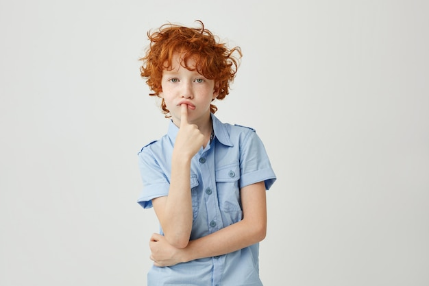 Portrait of funny little child with ginger wavy hair and freckles holding finger in mouth with bored face expression