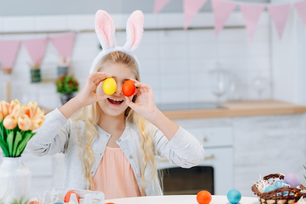 Portrait of funny little girl sitting at the table wearing bunny ears and closed her eyes by easter eggs
