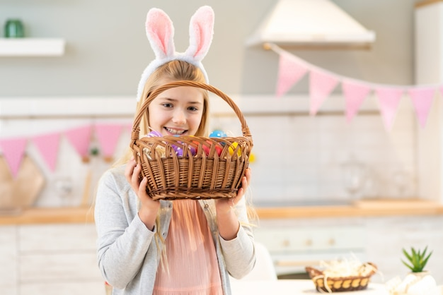 Portrait of funny little girl sitting at the table wearing bunny ears and holding easter basket with eggs