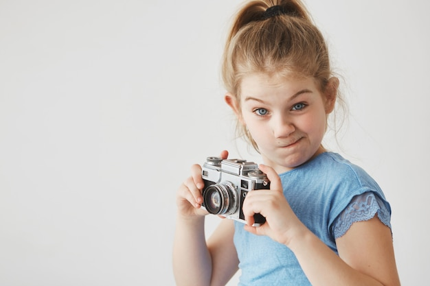 Portrait of funny little girl with blonde hair in tail hairstyle,  with silly expression, holding camera in hands going to take a picture.