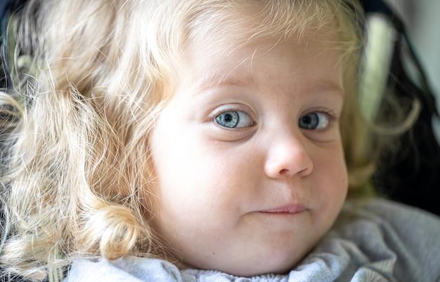 Ritratto di una bambina divertente con occhi azzurri e riccioli chiari.