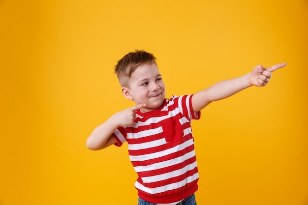 Portrait of a funny little kid pointing fingers away