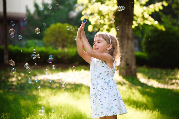 Portrait of funny lovely little girl with heterochromia two colored eyes blowing soap bubbles