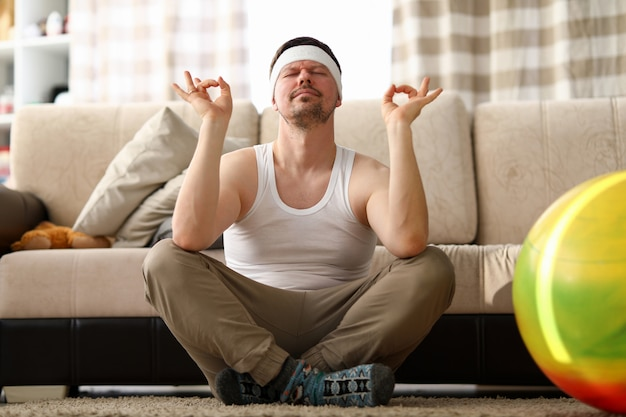 Portrait of funny male meditating at home
