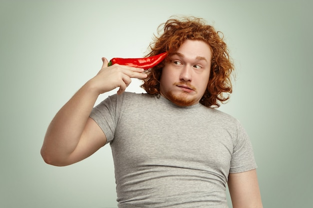 Portrait of funny male with ginger curly hair holding big red pepper at temple like gun