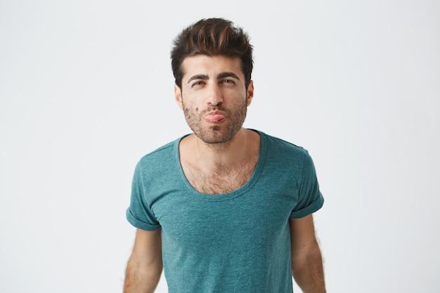 Ritratto di divertente ragazzo spagnolo maturo in maglietta blu, giocando sciocco mostrando la sua lingua e divertirsi al chiuso. espressioni del volto umano.