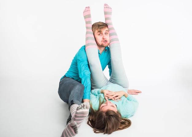 Портрет забавные моменты возбужденной пары, дурачящейся перед камерой на белой стене. весело, выходные и концепция дня святого валентина.