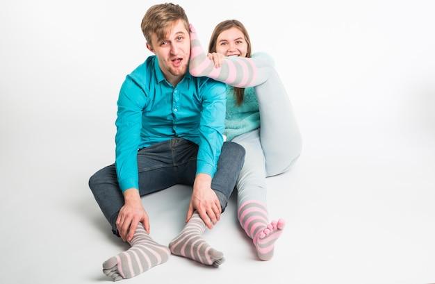 Портрет смешные моменты возбужденной пары, дурачящейся перед камерой на белой стене, весело