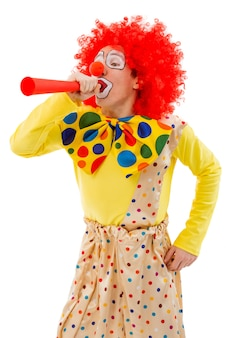 Portrait of a funny playful clown in red wig blowing horn.