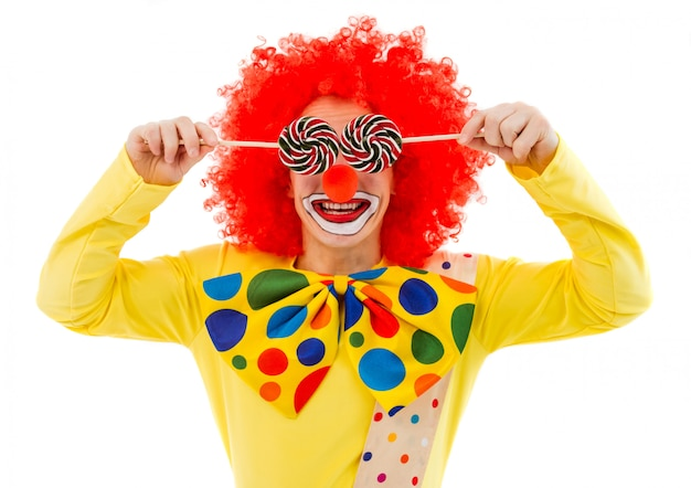 Portrait of funny playful clown in red wig covering his eyes