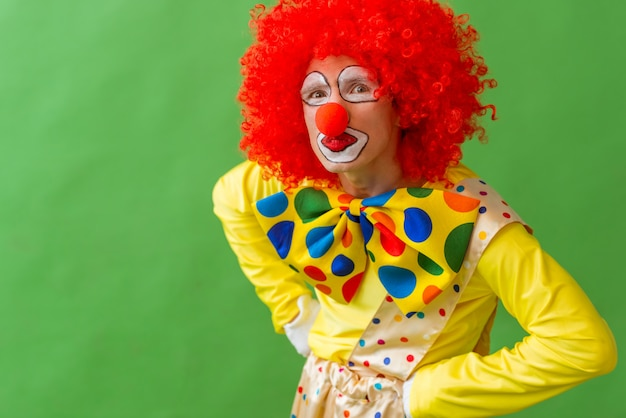 Portrait of a funny playful clown in red wig.