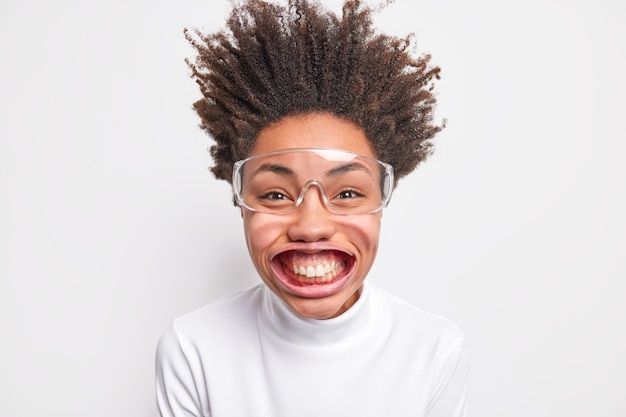 Portrait of funny positive dark skinned woman smiles with teeth has big mouh poses under air pressure has hair standing up dressed in casual poloneck and big transparent glasses