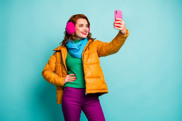 Portrait of funny pretty lady hold telephone hands taking selfies wear trendy casual ear covers yellow overcoat scarf magenta pants sweater.