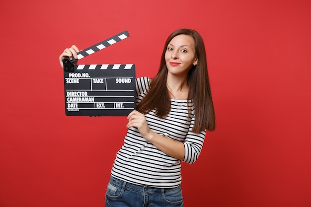 Portrait of funny pretty young woman in striped clothes holding classic black film making clapperboard isolated on bright red background. people sincere emotions lifestyle concept. mock up copy space.