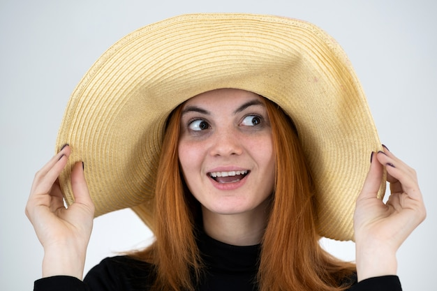 Portrait of funny redhead woman in bag straw hat.