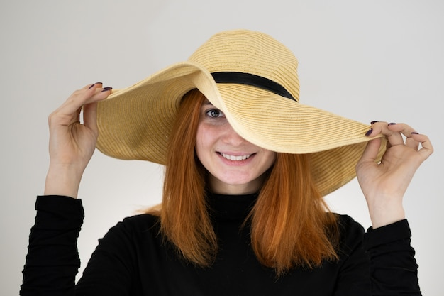 Portrait of funny redhead woman in bag yellow straw hat.