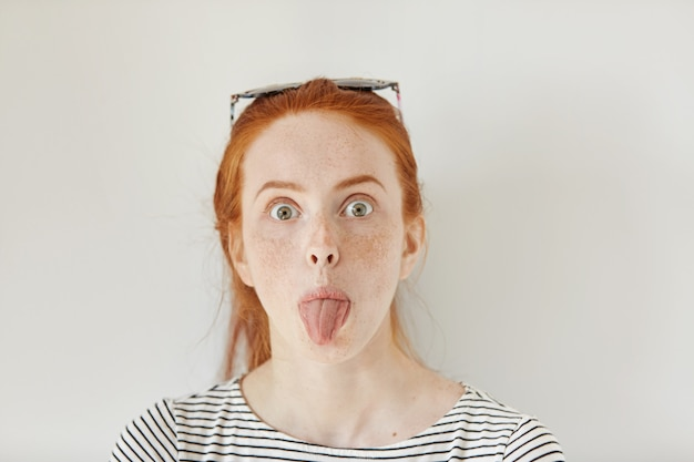 Portrait of funny redhead young caucasian woman with freckles having fun indoors, sticking out her tongue. close up of teenage girl wearing trendy sailor shirt making faces at white wall