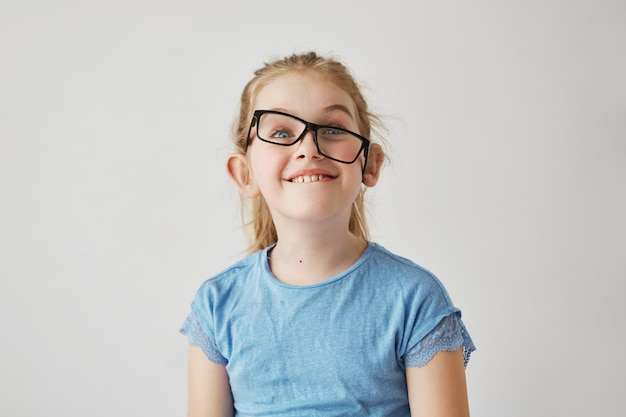 Portrait of funny small girl with blue eyes and light hair in blue shirt having fun with father's glasses. happy childhood concept.