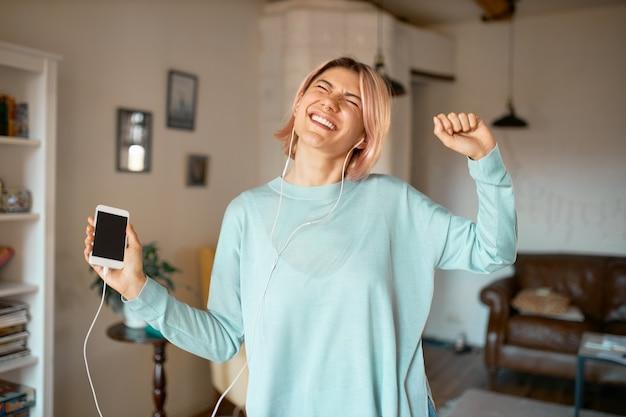 Ritratto di giovane donna alla moda divertente con capelli rosa che posa nell'interno accogliente dell'appartamento in auricolari