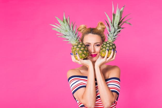 Portrait of funny woman and pineapple over pink background with copyspace.