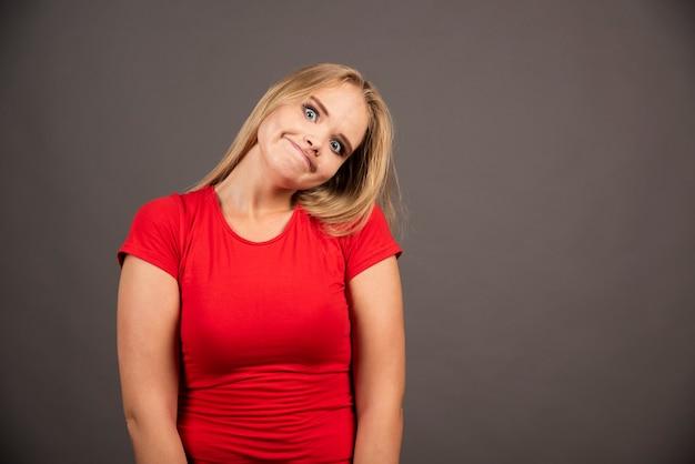 Portrait of funny woman posing over dark.