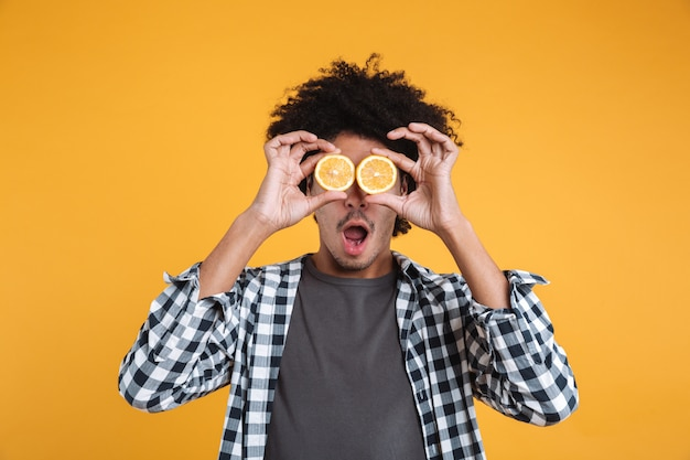 Portrait of a funny young african man holding sliced orange