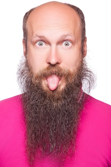 Portrait of a funny young bald, bearded man showing tongue, face expression.