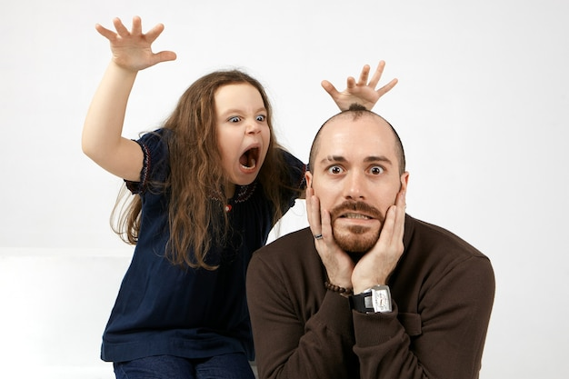 Portrait of funny young bearded male keeping hands on his face, being terrified by his little daughter who standing behind him, shouting