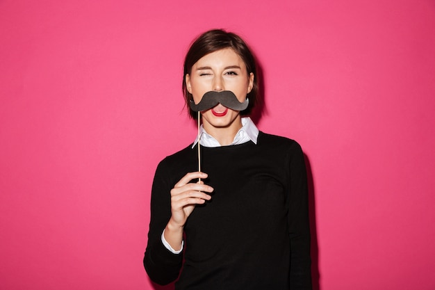 Portrait of a funny young businesswoman with paper moustache