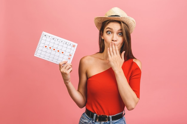 Portrait of a funny young girl holding periods calendar