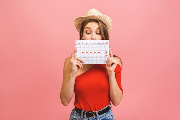 Portrait of a funny young girl in summer hat hiding behind a periods calendar isolated over pink background