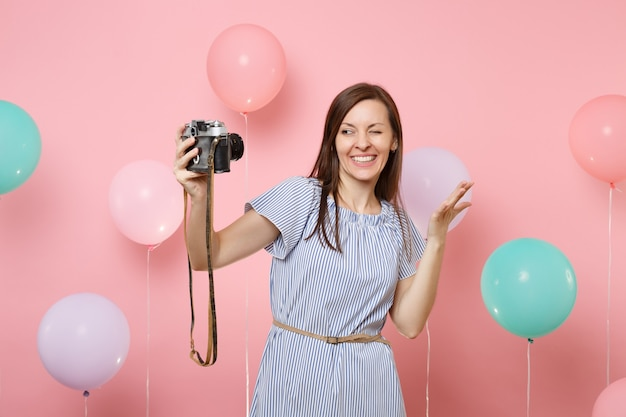 Portrait of funny young happy woman in blue dress doing selfie on retro vintage photo camera blinking spreading hands on pink background with colorful air balloons. birthday holiday party concept.