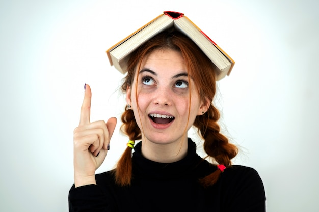 Portrait of funny young smiling student girl with an open book on her head holding her point finger up having an idea