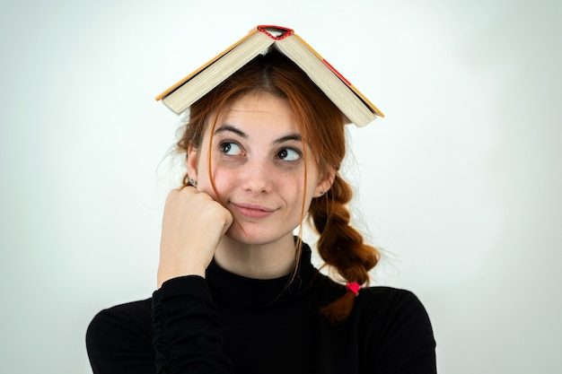 Portrait of funny young smiling student girl with an open book on her head. reading and education concept.