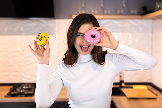 Portrait of funny young woman covering her eyes with donuts in modern kitchen.