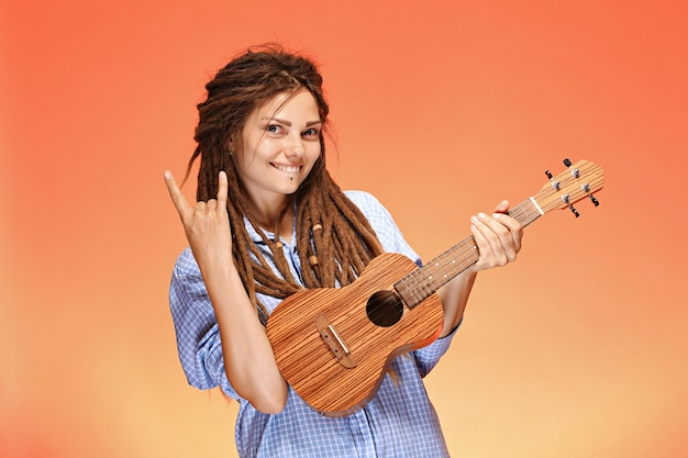 Portrait of funny young woman playing ukulele. happiness and carefree concept.