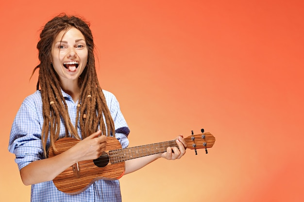Portrait of funny young woman playing ukulele happiness and carefree concept