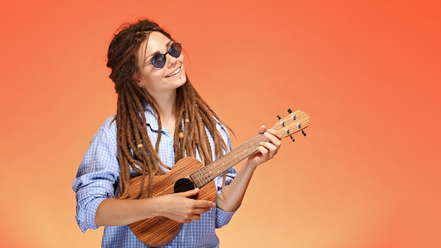 Portrait of funny young woman playing ukulele