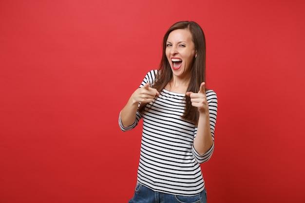 Ritratto di una giovane donna divertente in abiti a righe che urla, puntando il dito indice davanti