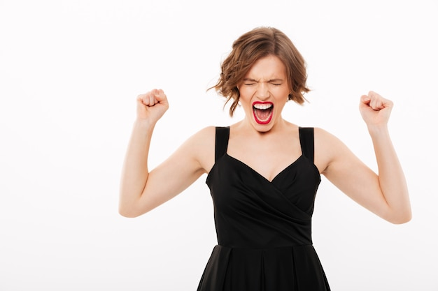 Portrait of a furious girl dressed in black dress screaming