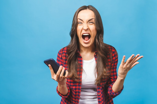 Portrait of a furious young business woman yelling at mobile
