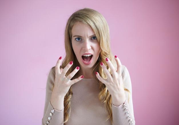 Ritratto di giovane donna di affari furiosa con unghie rosse e capelli biondi ondulati che urla, mantenendo la bocca ampiamente e facendo un gesto arrabbiato, arrabbiandosi con i suoi dipendenti inefficaci. concetto di rabbia, furia e rabbia